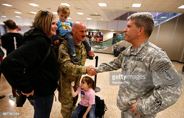 SSG Chuck Hoffman his wife Mundy kids Wade and Mikaela are greeted by unit commander Sgt Major Steve Wooldridge as members of the Utah National...