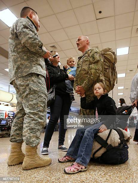 SSG Chuck Hoffman talks to a public affairs officer as his wife Mundy kids Wade and Mikaela wait as members of the Utah National Guard's 19th Special...
