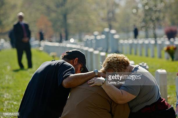 Chuck Jackson and Kimberly Shrauger comfort Kimberly's husband Lowell Shrauger as he visits the grave of his lifelong friend Staff Sgt Jamie L...