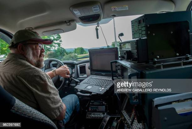 Chuck Niday an radio frequency technician monitors equipment as he looks for telecommunication signals and violators as he drives his truck in Green...