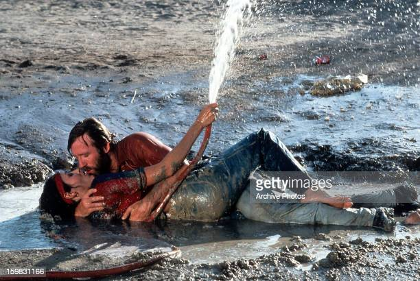 Chuck Norris and Barbara Carrera having a passion moment while laying in some man made mud in a scene from the film 'Lone Wolf McQuade' 1983
