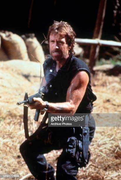 Chuck Norris attacking with a fire arm in a scene from the film 'Delta Force 2' 1990