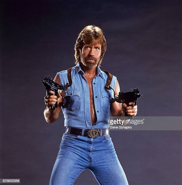 Chuck Norris poses with two Uzis, his sleeveless denim shirt unbuttoned to his waist. Publicity for Invasion USA