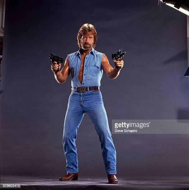 Chuck Norris poses with two Uzis his sleeveless denim shirt unbuttoned to his waistPublicity for Invasion USA