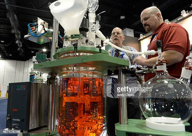Chuck Sanders a biochemistry professor at Vanderbilt University left looks over a process chemical reactor with Chemglass Life Sciences Colorado...