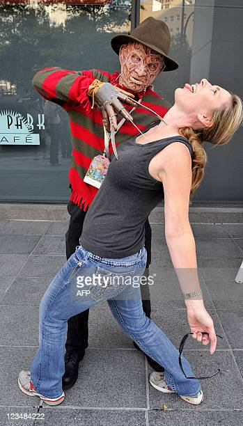 Chuck Visgner decked out as the Freddie Kreuger slashes at victim Joyce Bone before the start of the Dragoncon parade on September 3 in Atlanta...