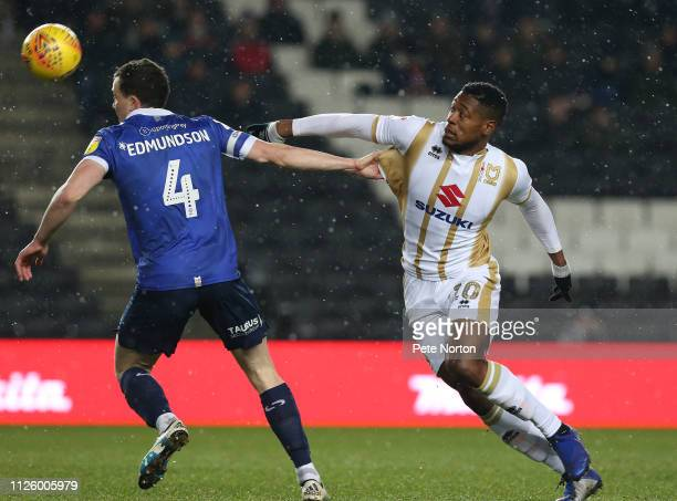 Chuks Aneke of Milton Keynes Dons contests the ball with George Edmundson of Oldham Athletic during the Sky Bet League Two match between Milton...