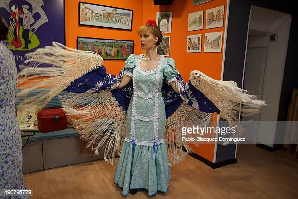 'Chulapa' Paloma Clemente dress up her manila shawl at the 'Association of Rompe y Rasga' premises during the San Isidro festivities before their way...