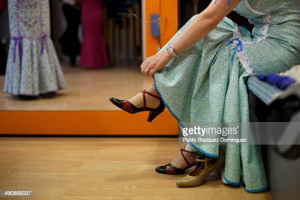 'Chulapa' Paloma Clemente prepares her dress at the 'Association of Rompe y Rasga' premises during the San Isidro festivities before making her way...