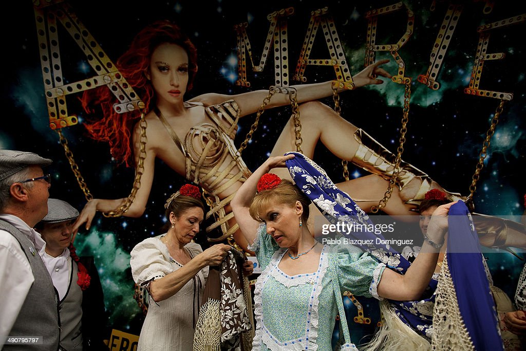 'Chulapas' Natividad Hipolito (3L) and Paloma Clemente (2R) dress their manila shawl during the San Isidro festivities as they wait for a train on their way to Pradera de San Isidro park on May 15, 2014 in Madrid, Spain. During the festivities in honor of San Isidro Labrador in Madrid revelers take the streets and enjoy music and popular food. Chulapos or Goyescos dance the regional dance known as 'chotis' wearing traditional costumes of Madrid.