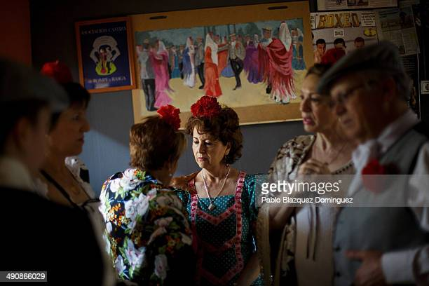 'Chulapos and chulapas' chat at the 'Association of Rompe y Rasga' premises during the San Isidro festivities before making their way to Pradera de...