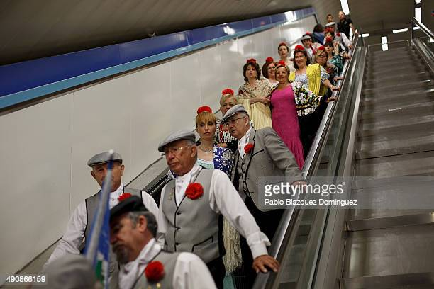'Chulapos' and 'chulapas' from the 'Association of Rompe y Rasga' use scalators in the underground during the San Isidro festivities as they make...