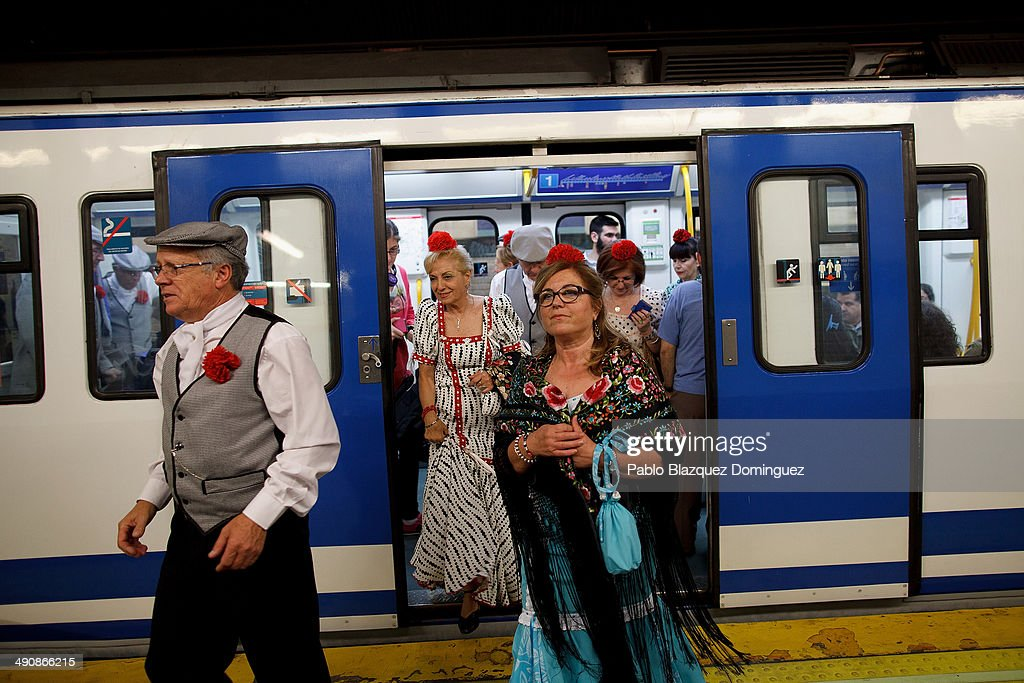 'Chulapos' and 'chulapas' walk out from a train during the San Isidro festivities on their way to Pradera de San Isidro park on May 15, 2014 in Madrid, Spain. During the festivities in honor of San Isidro Labrador in Madrid revelers take the streets and enjoy music and popular food. Chulapos or Goyescos dance the regional dance known as 'chotis' wearing traditional costumes of Madrid.