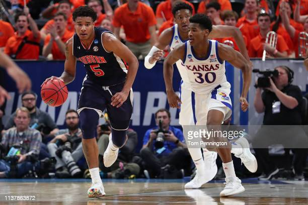 Chuma Okeke of the Auburn Tigers dribbles the ball as Ochai Agbaji of the Kansas Jayhawks chases after him during their game in the Second Round of...