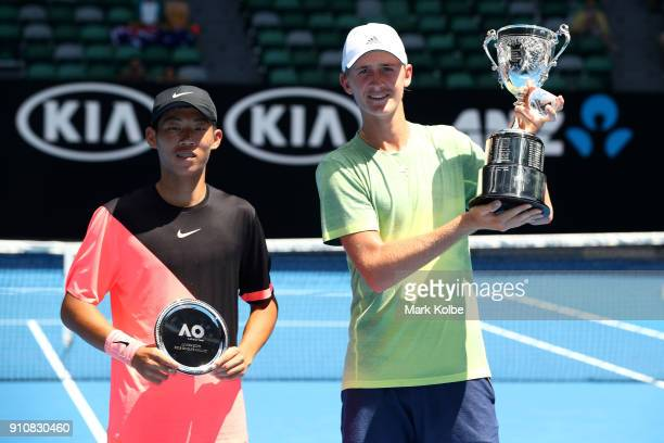 Chun Hsin Tseng of Chinese Taipei poses with the runnersup trophy and Sebastian Korda of the United States poses with the championship trophy after...