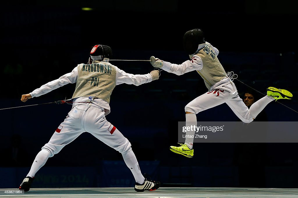 Chun Yin Ryan Choi of Hong Kong (L) and Andrzej Rzadkowski of Poland compete in the Men's Foil Individual Gold Medal Bout on day three of the Nanjing 2014 Summer Youth Olympic Games at Nanjing International Expo Centre on August 19, 2014 in Nanjing, China.