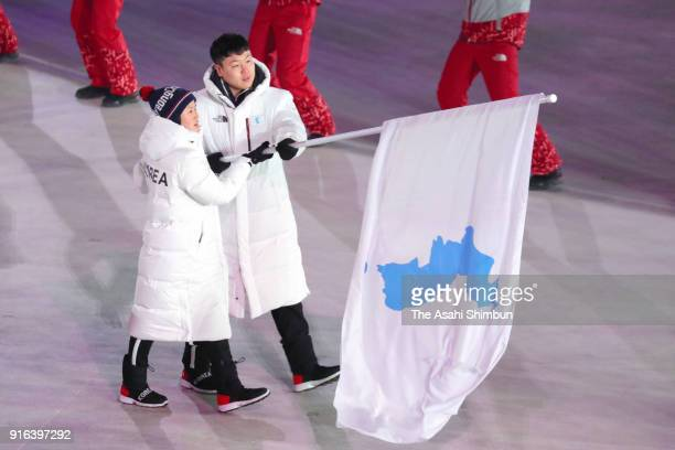 Chung Guam Hwang of North Korea and Yunjong Won of South Korea lead the team under the unified flag during the Opening Ceremony of the PyeongChang...