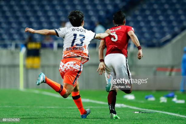 Chung Woon of Jeju United and Tomoaki Makino of Urawa Reds Diamonds during the AFC Champions League Round of 16 match between Urawa Red Diamonds and...