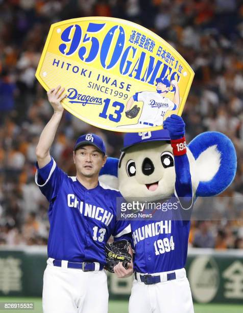Chunichi Dragons' pitcher Hitoki Iwase holds up a board showing his 950th appearance in games after pitching against the Yomiuri Giants at Tokyo Dome...