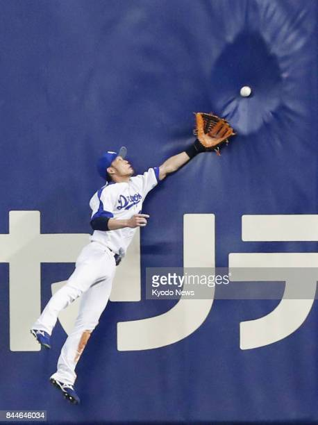 Chunichi Dragons right fielder Atsushi Fujii jumps as a ball batted by Xavier Batista of the Hiroshima Carp hits a fence for a double in the sixth...
