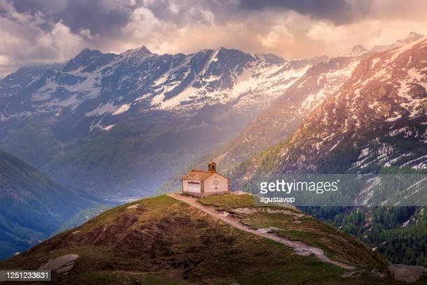 chiesa sopra l'idilliaco paesaggio alpino italiano - gran paradiso, italia - parco nazionale del gran paradiso foto e immagini stock