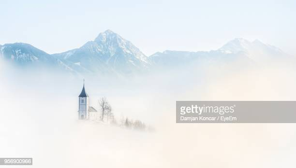 church amidst fog against mountains - kranj stock pictures, royalty-free photos & images