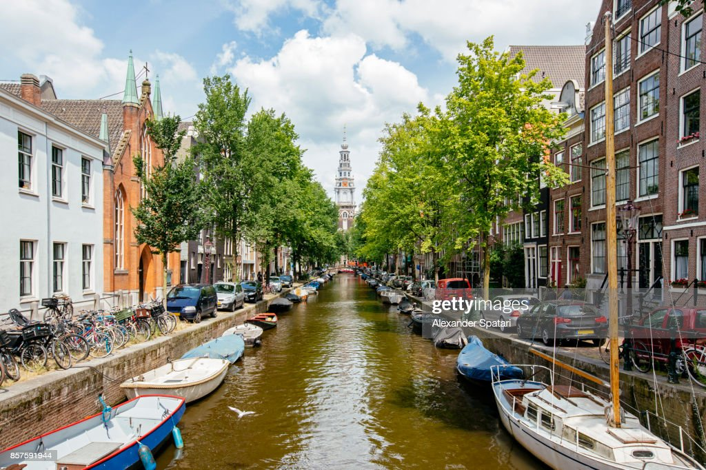 Church and boats moored along the canal in Amsterdam, Holland : Stock Photo