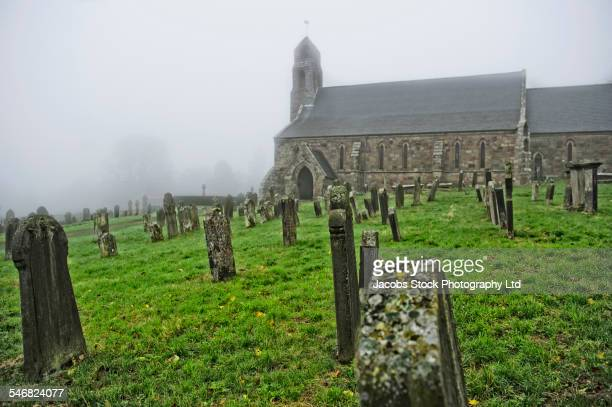 Church and gravestones in foggy cemetery