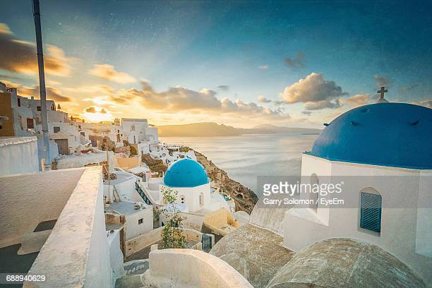 church and houses in town by sea at santorini during sunrise - islas griegas fotografías e imágenes de stock