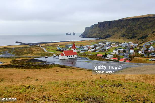 Church and village of Vik (Vik i Myrdal) and Reynisdrangar sea stacks in distance, Iceland