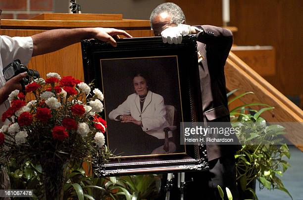Church assistant George Wilson <cq> picks up the picture of Rachel Bassette Noel that was surrounded by flowers for the service A memorial service...