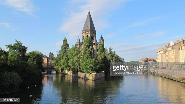 church by canal against sky in city - moselle stockfoto's en -beelden