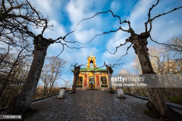 church by trees and building against sky - drottningholm palace stock pictures, royalty-free photos & images