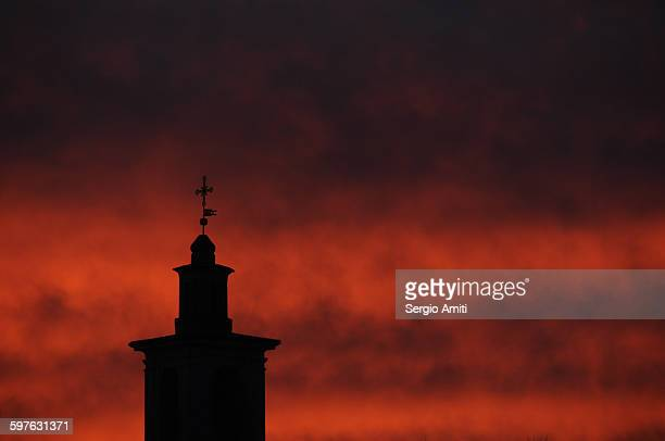 A church clocktower silhouetted against red sky
