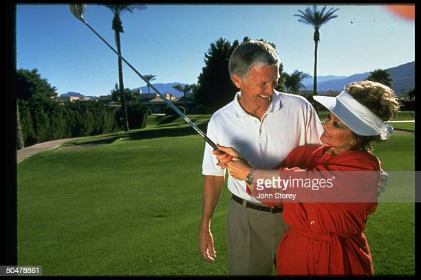 Church developer Roe Messner w arm around TV talk show host wife Tammy Faye Messner as she swings golf club nr their home