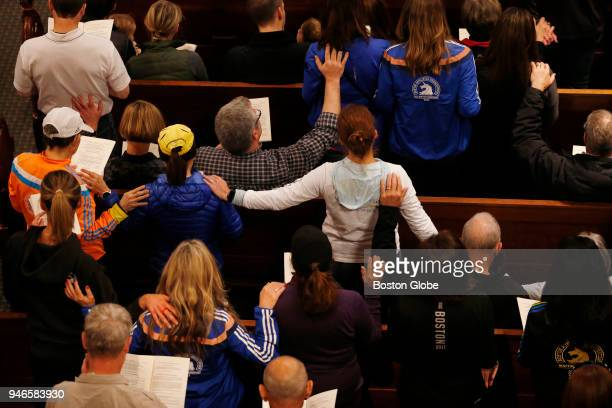 Church goers place their hands on the runners during a special The Blessing of the Athletes service at the Old South Church on April 15 the five year...