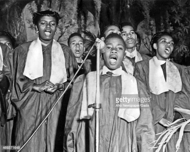 A church gospel choir with a boy at the microphone as the lead singer 1950