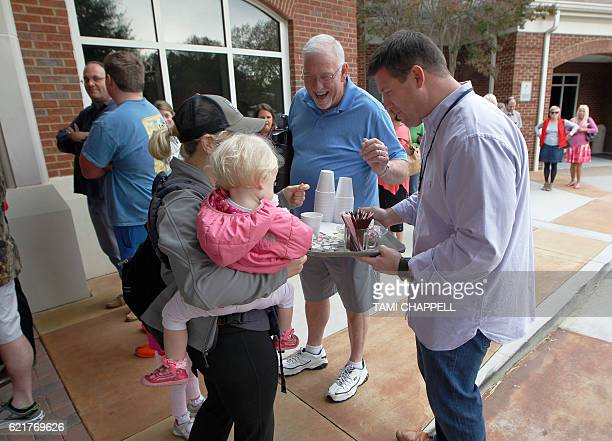 Church members Jay Hackett and his father Jerry Hackett hand out coffee to voters standing in line including Angie Murphy and her daughter Maggie at...