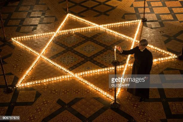 A church minister lights a candle as 600 candles depicting the Star of David are set out during an event to commemorate Holocaust Memorial Day 2018...