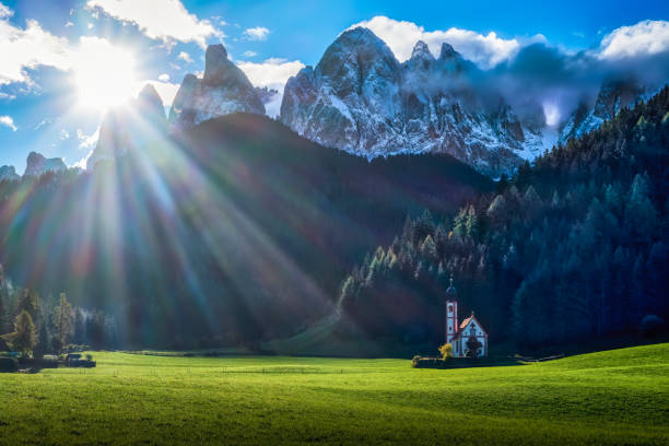 Church of San Giovanni in Ranui at Funes Valley with the mountains of Geisler Gruppe in the background, Dolomites, Trentino-Alto Adige, Italy