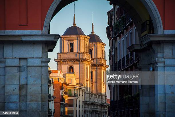Church of San Isidro through one of the arches of the Plaza Mayor of Madrid