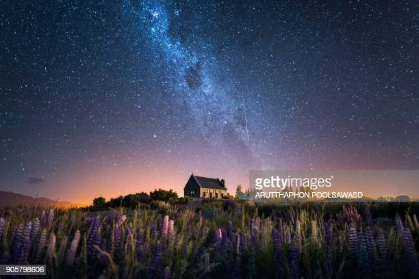 church of the good shepherd and milky way with lupins blooming, lake tekapo, new zealand - naturwunder stock-fotos und bilder