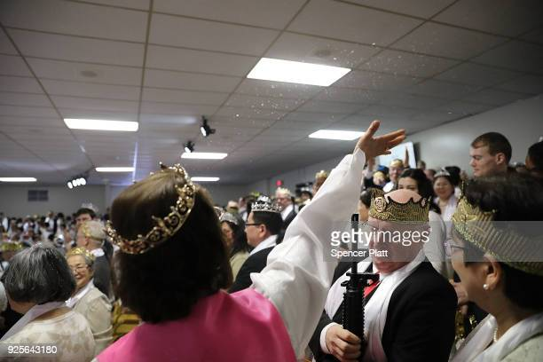 A church offical throws water during a ceremony at the World Peace and Unification Sanctuary in Newfoundland Pennsylvania on February 28 2018 in...