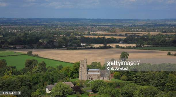 church on a hill in a landscape of farmland and countryside - land stock pictures, royalty-free photos & images
