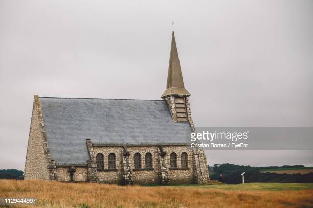 church on field against sky - bortes stock pictures, royalty-free photos & images