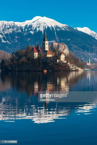 église sur l'île de bled de lac contre les alpes juliens - slovénie photos et images de collection