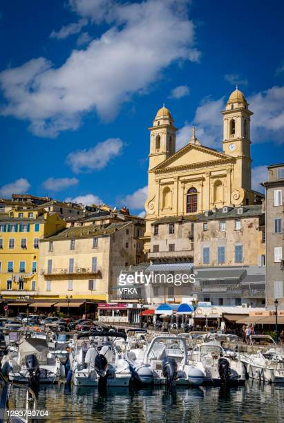 church saint-jean baptiste and the old harbor (vieux-port) of bastia, corsica, france after sunset. - vertical stock pictures, royalty-free photos & images