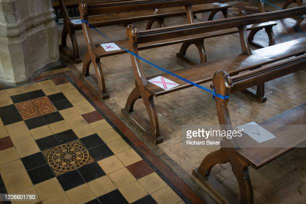 Church seating pews are marked with ticks and crosses marking where parishioners are allowed to sit according to Coronavirus pandemic lockdown...