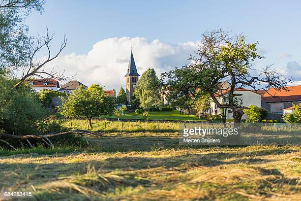 church spire and village field in launstroff - moselle france stock pictures, royalty-free photos & images