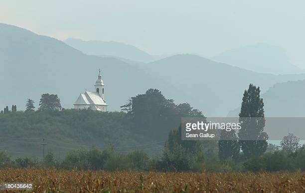 A church stands on a hilltop as the western Romanian Carpathian mountains stand behind in the Transylvania region on September 11 2013 near...